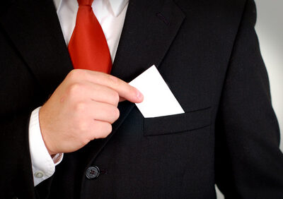 A businessman in a suit holds a blank white business card that is ready for your logo!
